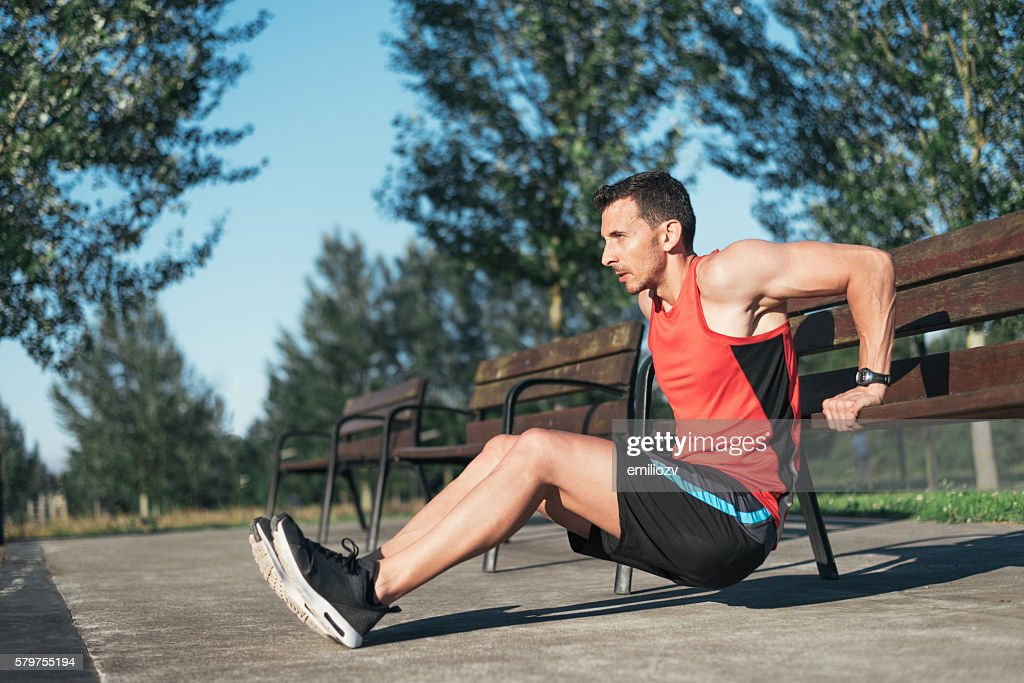 Fitness man doing bench triceps dips outdoors while working out : Stock Photo