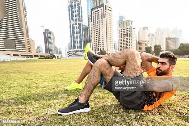 Fitness man doing cruch abs in Dubai marina