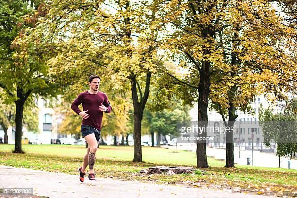 Fitness Mann laufen in Berlin unter dem Regen in den Herbst