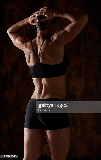 fitness model showing off her back - black female bodybuilder stock photos and pictures
