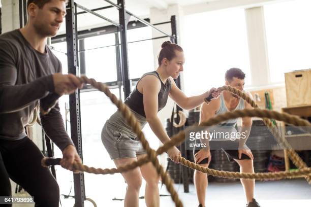 Fitness people working out with battle ropes at gym