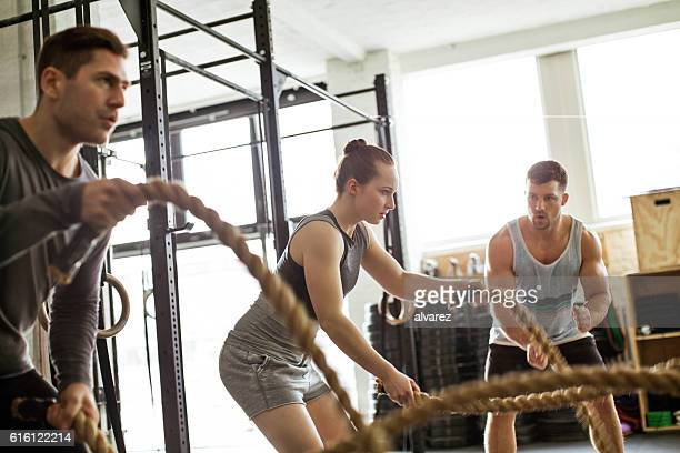 fitness people working out with battle ropes - crossfit stock pictures, royalty-free photos & images