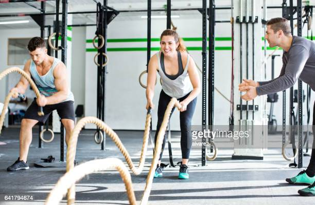 fitness people working out with battle ropes - small group of people stock pictures, royalty-free photos & images