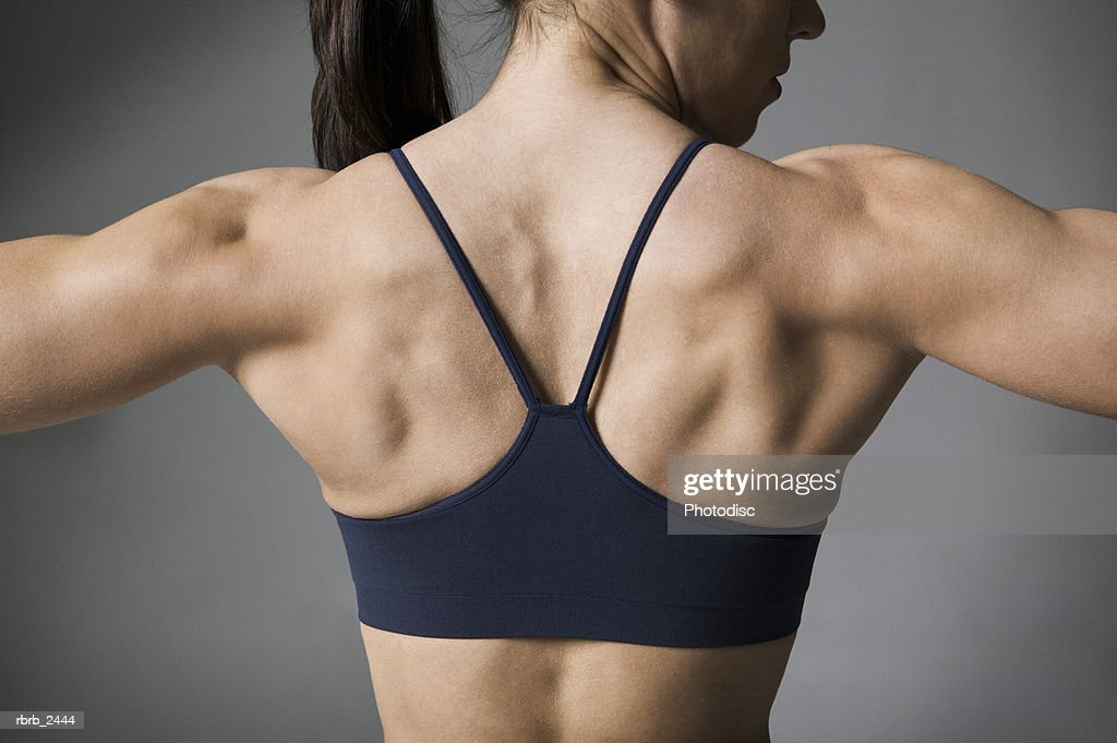 fitness portrait of a muscular female in a black workout outfit as she flexes her muscles : Foto de stock