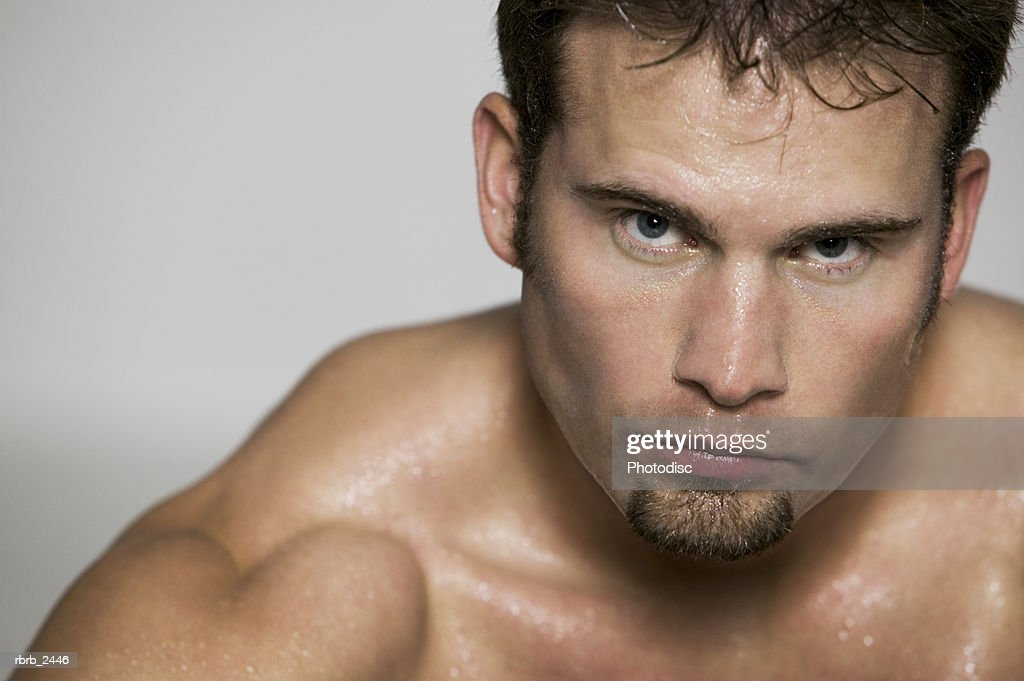 fitness portrait of a muscular shirtless male as he glares at the camera : Foto de stock