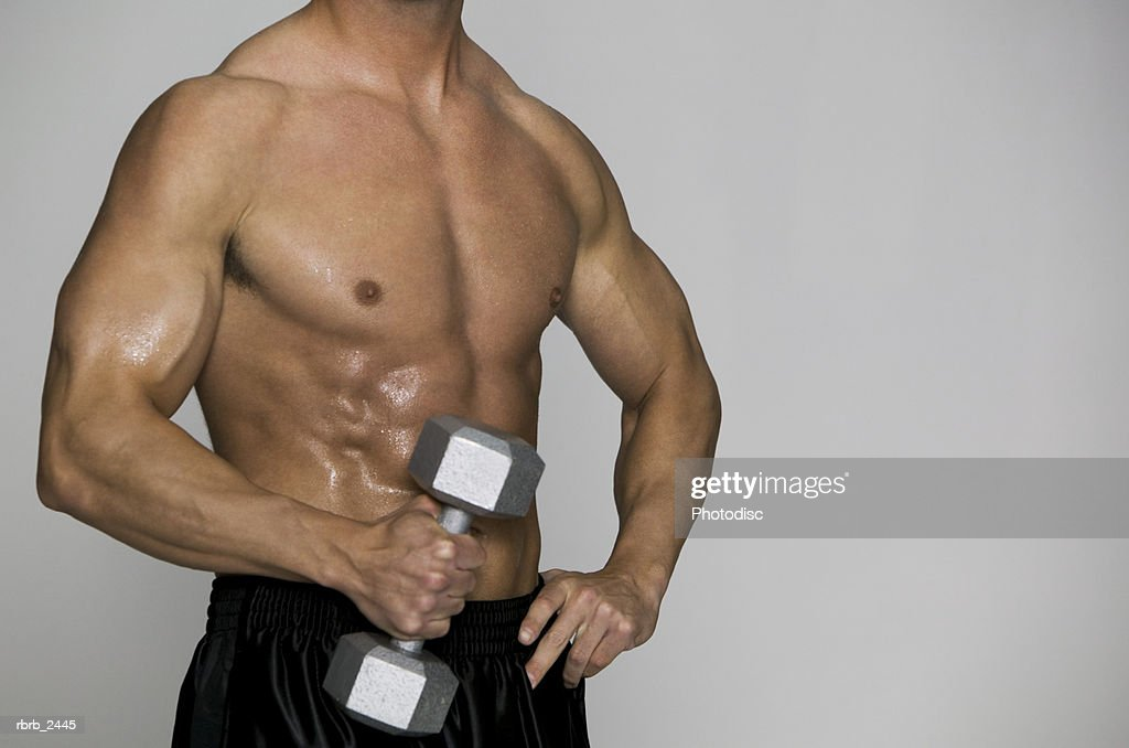 fitness portrait of a muscular shirtless male as he holds a small weight : Foto de stock