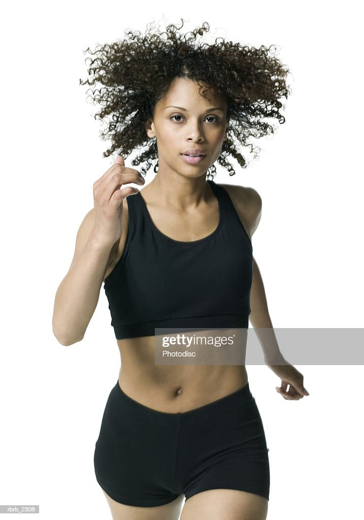 fitness portrait of a young adult female in a black workout outfit as she jogs : Stock Photo