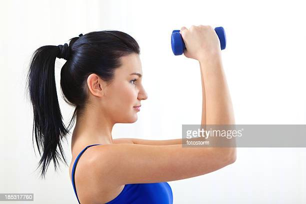 Fitness series - Young woman lifting weights