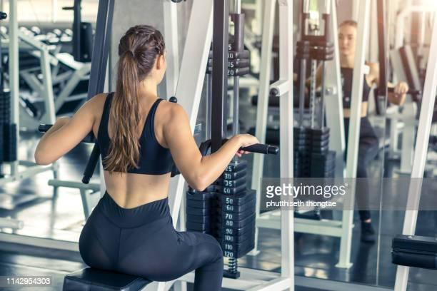 fitness, sport, training and lifestyle concept - young women flexing muscles  in fitness gym center - beautiful woman chest stock pictures, royalty-free photos & images