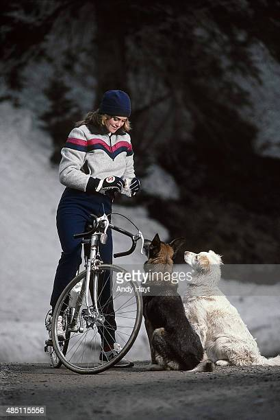 Sporting Look Portrait of model Kathy Ireland feeding dogs aboard bicycle while wearing fleece pullover by Levi's Skiwear and pants by North Face...