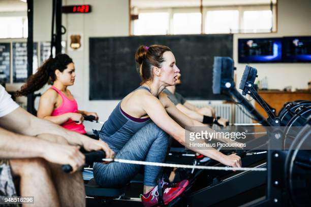 fitness team using rowing machines together - 練習 ストックフォトと画像