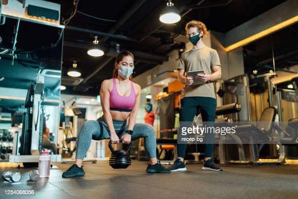 fitness trainer che controlla le condizioni dell'atleta in palestra mentre entrambe indossano maschere protettive per la prevenzione delle malattie - opening event foto e immagini stock