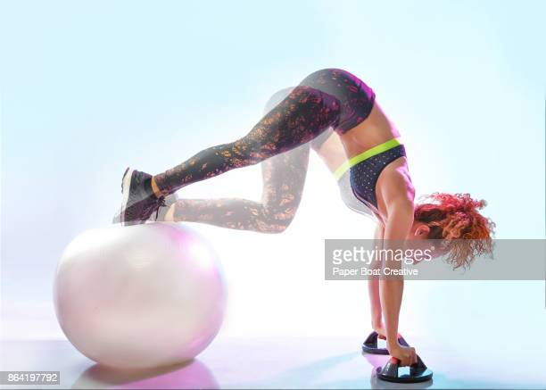 fitness trainer demonstrating various uses of exercise using the swiss ball - pike position stock photos and pictures