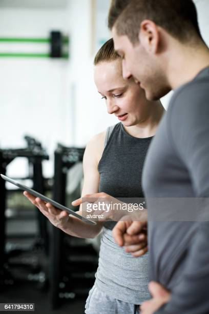 Fitness trainer discussing workout plan with client