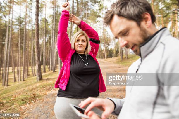 fitness trainer in park tracking progress of overweight woman running down the stairs. - fat blonde women stock photos and pictures