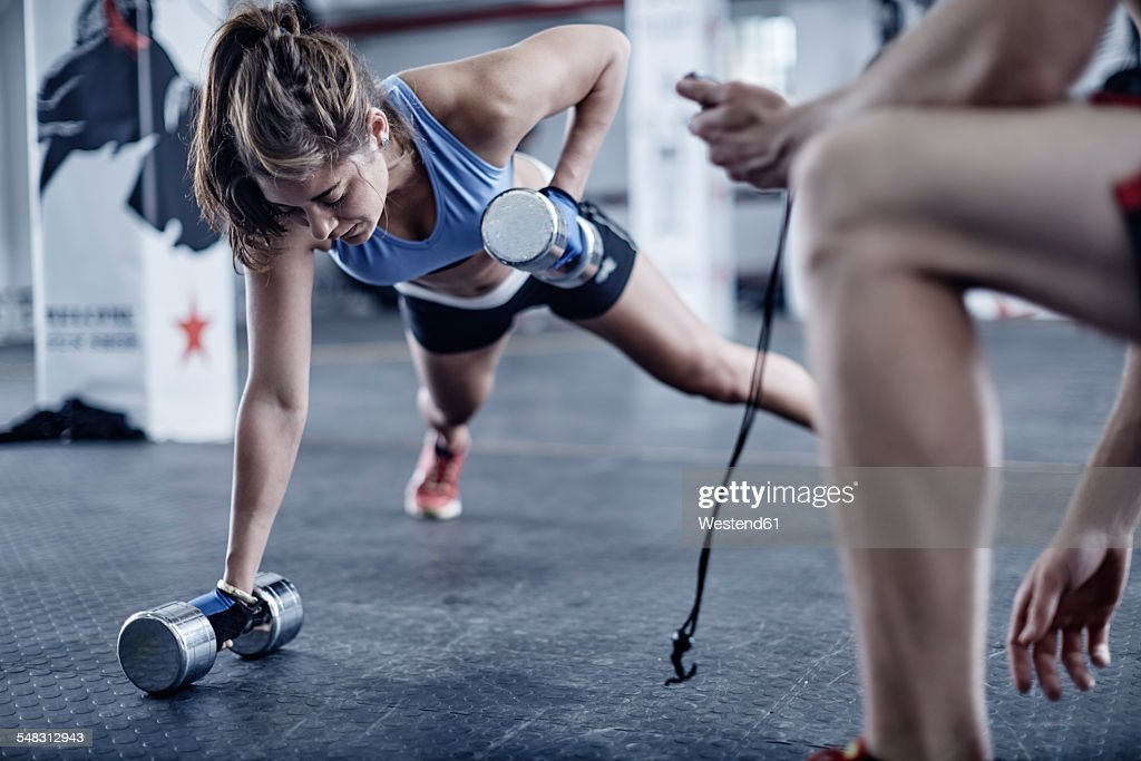 Fitness trainer keeping time with woman doing dumbell push-ups : Stock Photo