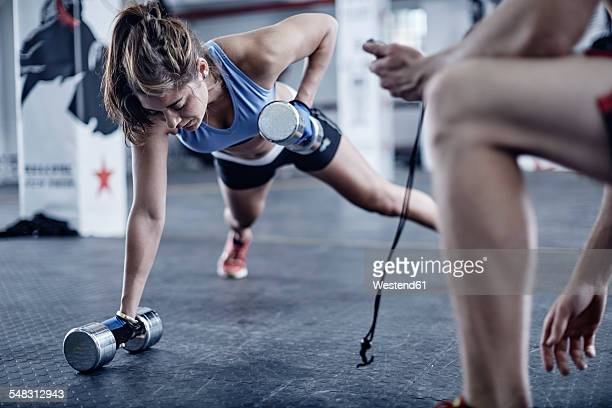 fitness trainer keeping time with woman doing dumbell push-ups - entrenador fotografías e imágenes de stock