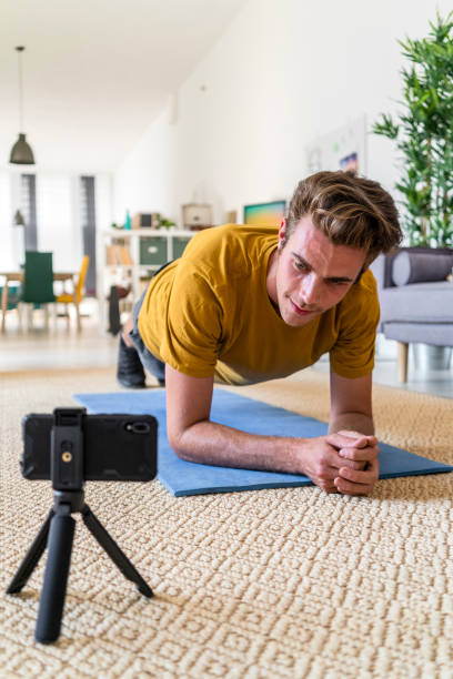 Fitness trainer live streaming plank exercise at home