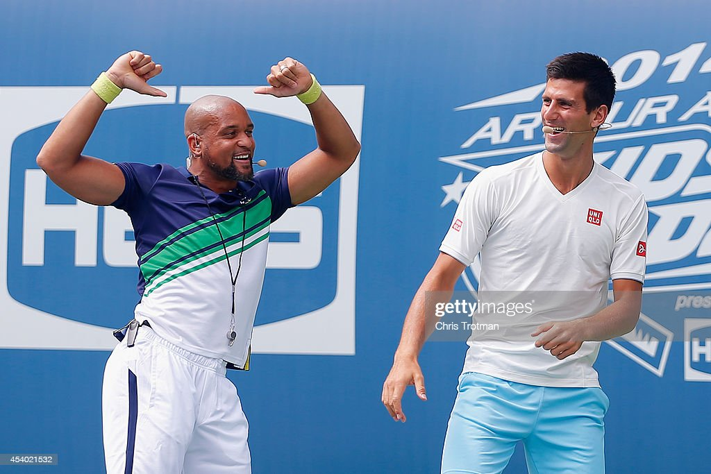 Fitness trainer Shaun T and Novak Djokovic of Serbia dance during Arthur Ashe Kids' Day prior to the start of the 2014 U.S. Open at the USTA Billie Jean King National Tennis Center on August 23, 2014 in the Flushing neighborhood of Queens in New York City.
