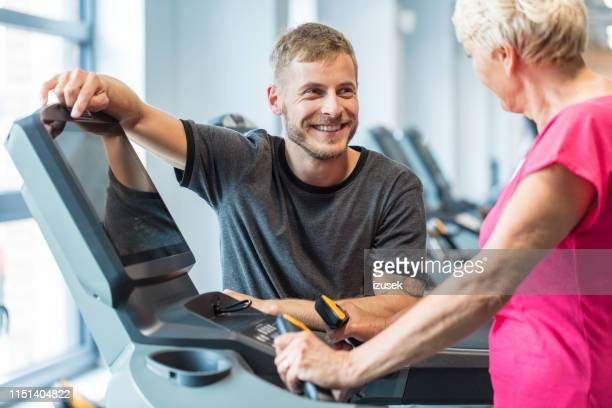 fitness trainer talking with senior woman exercising at rehab - drug rehab stock pictures, royalty-free photos & images
