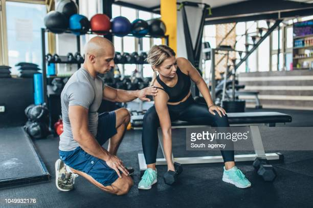 fitness trainer teaching girl weightlifting - fitness instructor stock pictures, royalty-free photos & images