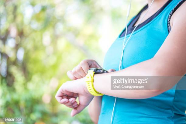 fitness woman checks results after workout session on smartwatch on fitness application. - 女性選手 ストックフォトと画像