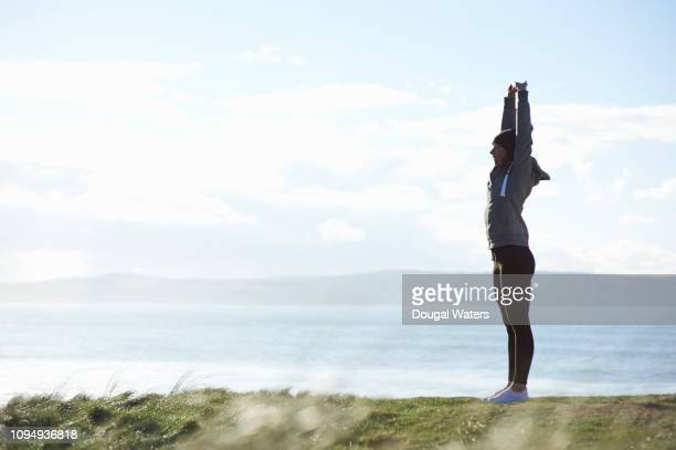 fitness woman on coastline stretching arms above head. - dougal waters stock pictures, royalty-free photos & images