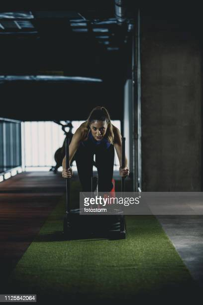 Fitness woman pushing weighted sled