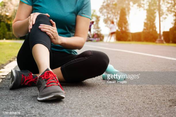 fitness woman runner feel pain on knee. outdoor exercise activit - human body part ストックフォトと画像