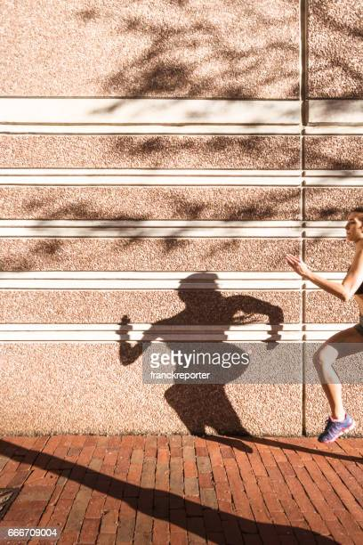 fitness woman running against the wall - extra long stock pictures, royalty-free photos & images