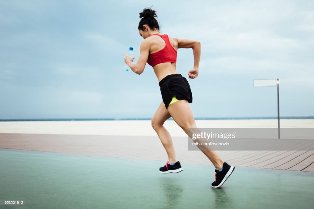 Fitness woman running at the beach coast : Stock Photo