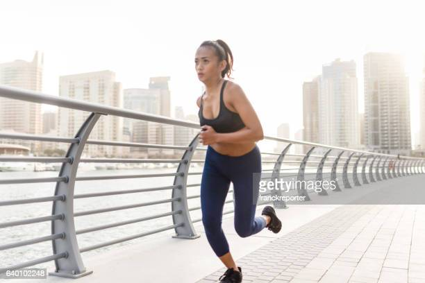 fitness woman running in dubai marina - filipino culture stock pictures, royalty-free photos & images