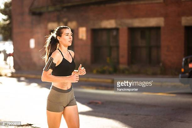 Fitness Woman running on the city against the wall