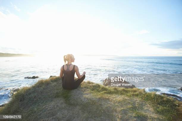 fitness woman sitting looking out to sea from coastal viewpoint. - dougal waters stock pictures, royalty-free photos & images