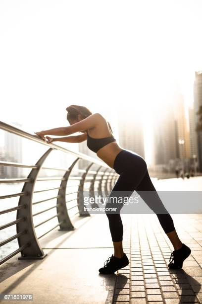 fitness woman stretching in dubai marina - fat belly girl stock photos and pictures