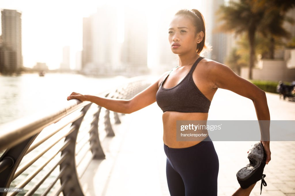 fitness woman stretching in dubai marina : Stock Photo