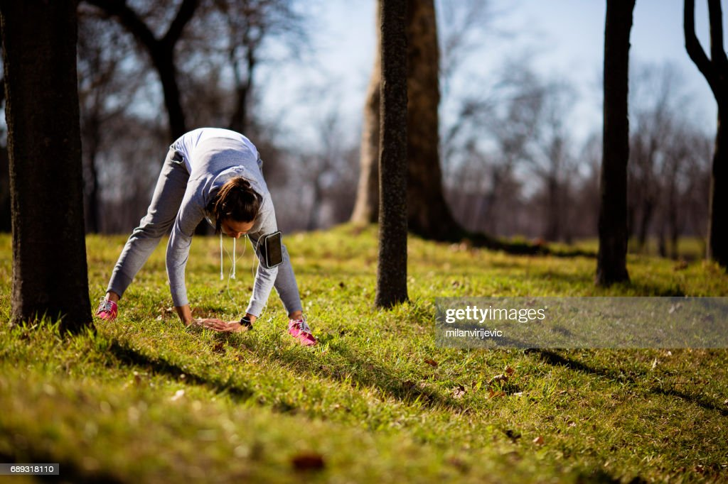 Fitness woman stretching in nature : Stock Photo