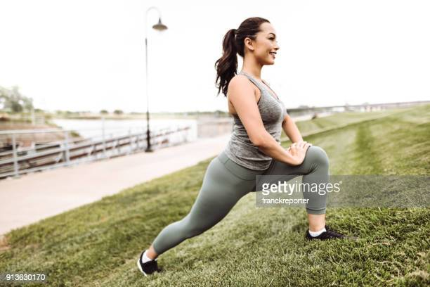 fitness woman stretching in the grass - curvy women stock pictures, royalty-free photos & images