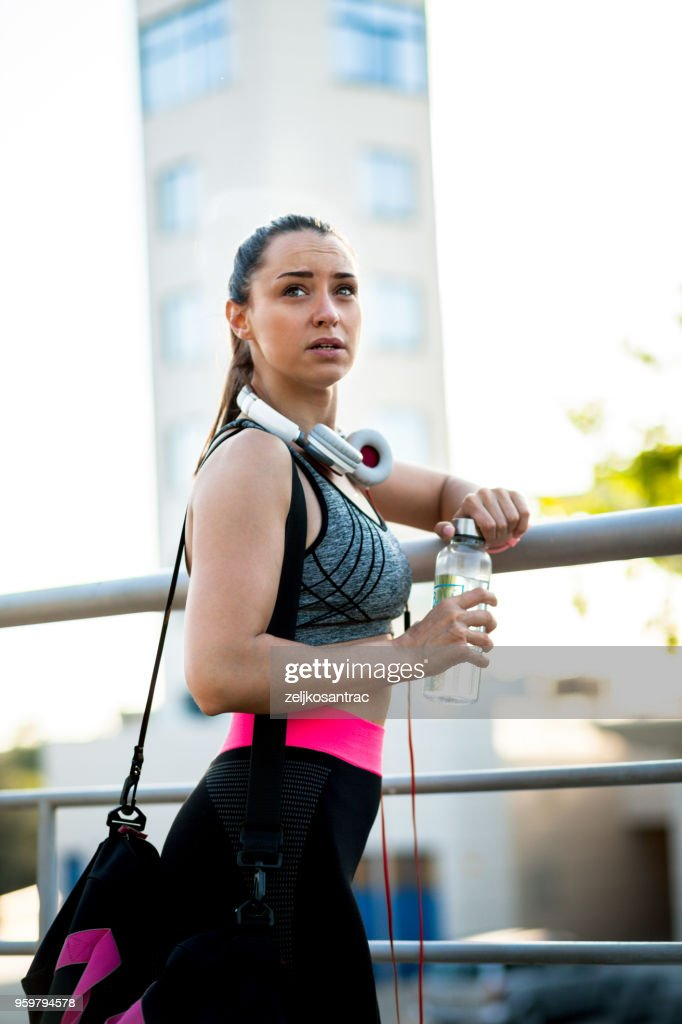 Fitness woman taking a break after running workout : Stock Photo