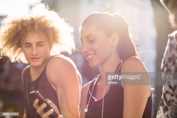 Fitness woman using mobile phone with her friends