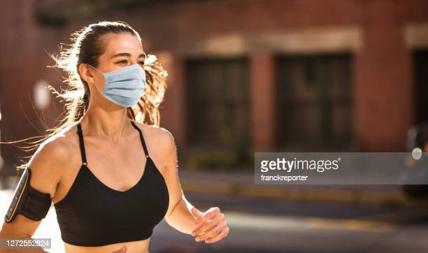 mulher fitness usando máscara facial durante o confinamento - corrida esportiva - fotografias e filmes do acervo