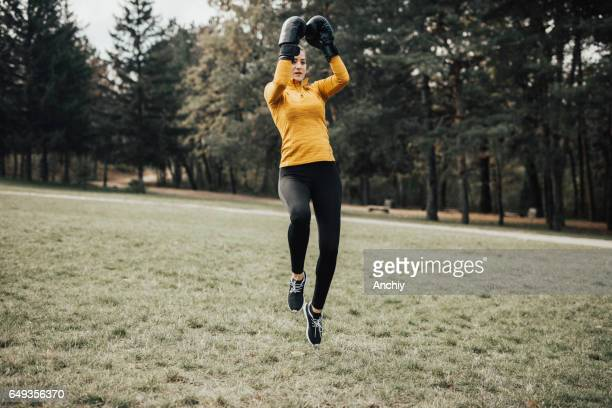 Fitness woman with boxing gloves training outdoors