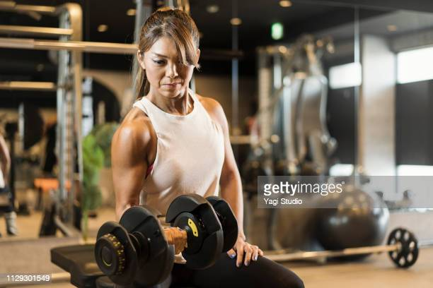 fitness woman working out at private gym - asian female bodybuilder stock photos and pictures