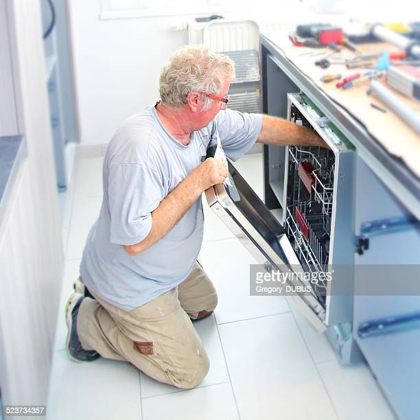 Fitter installing dishwasher in kitchen