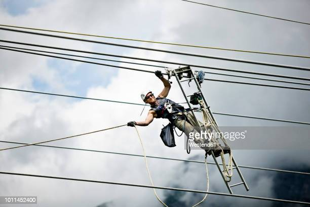 fitter with ladder, pulling along high-voltage power line - pericolo foto e immagini stock