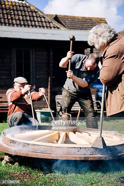 Fitting the metal tyre onto a wooden cartwheel, sledgehammer, wheelwrights
