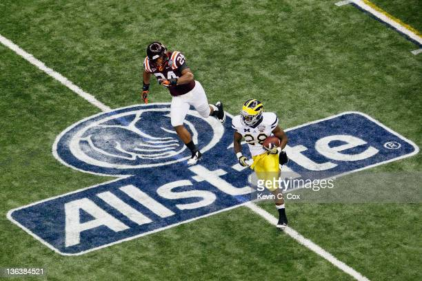 Fitzgerald Toussaint of the Michigan Wolverines runs with the ball in the first quarter against Tariq Edwards of the Virginia Tech Hokies during the...