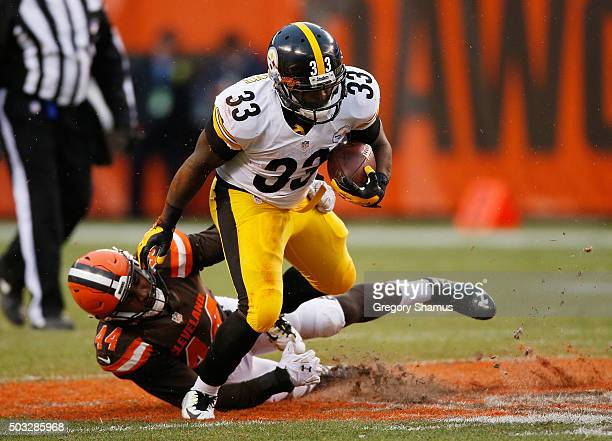 Fitzgerald Toussaint of the Pittsburgh Steelers avoids a tackle by Nate Orchard of the Cleveland Browns during the fourth quarter at FirstEnergy...