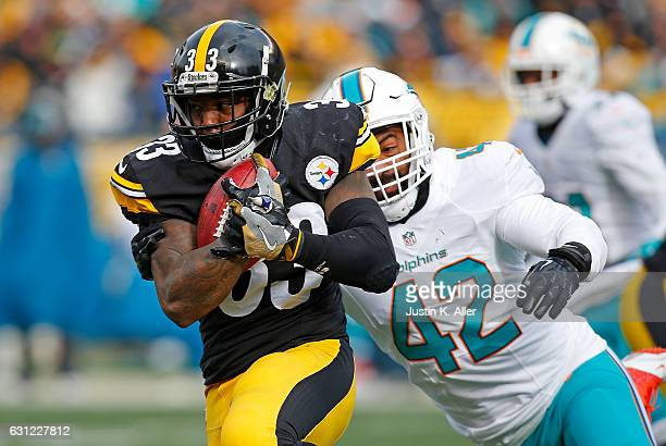 Fitzgerald Toussaint of the Pittsburgh Steelers rushes against Spencer Paysinger of the Miami Dolphins in the first half during the Wild Card Playoff...