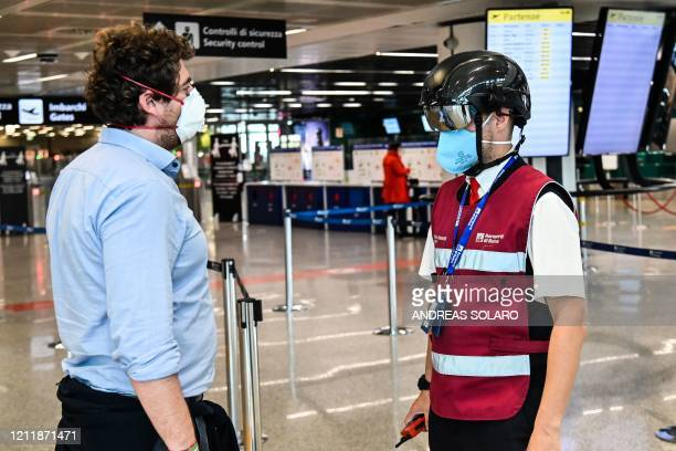 Fiumicino airport employee wearing a SmartHelmet portable thermoscanner to screen passengers and staff for COVID19 scans a fellow airport staff at...
